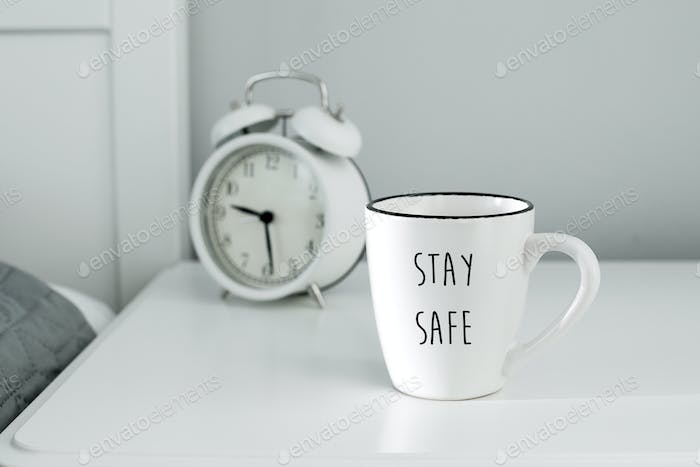 Morning home routine. White cup of coffee and alarm clock. Stay home, stay safe, quarantine concept.