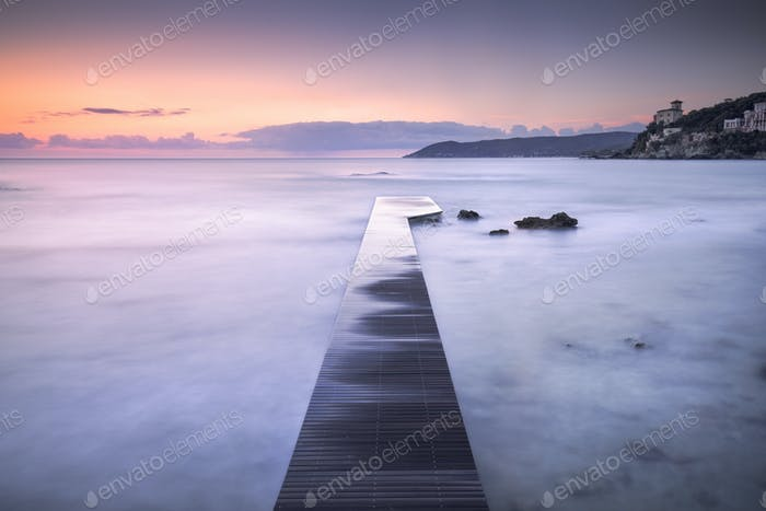 Castiglioncello bay wooden pier, rocks and sea on sunset. Tuscan