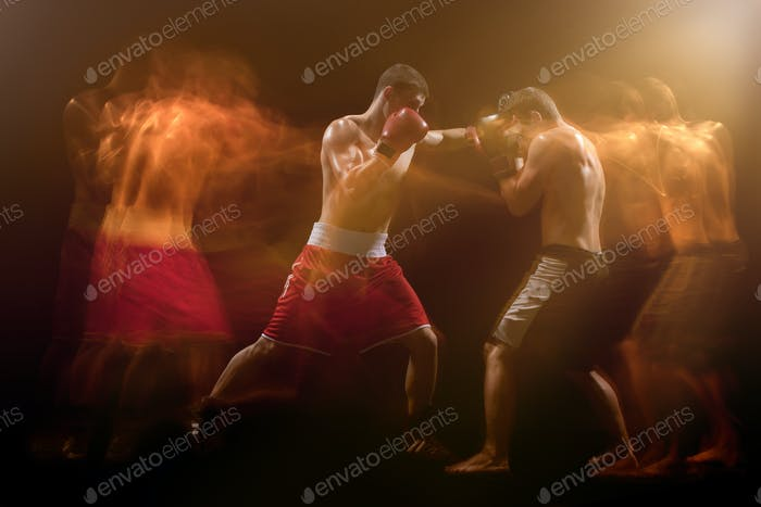 The two male boxers boxing in a dark studio