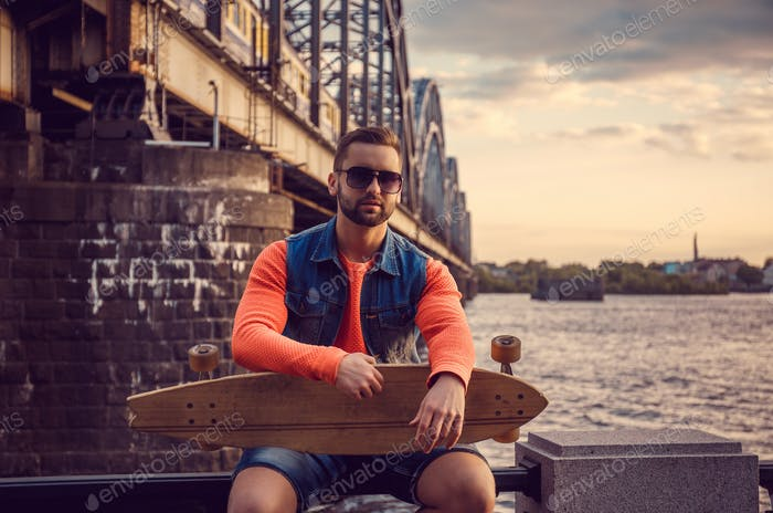 Casual male with longboard posing near river.