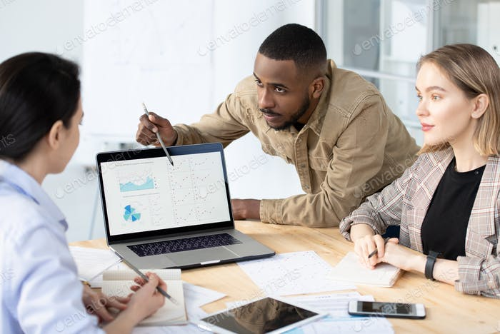 Young confident banker or broker bending over desk while analyzing data