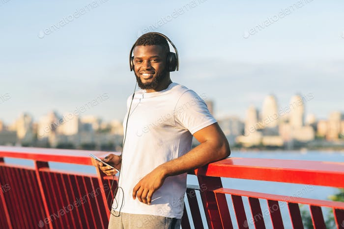 Handsome afro sportsman smiling at camera, staying on bridge