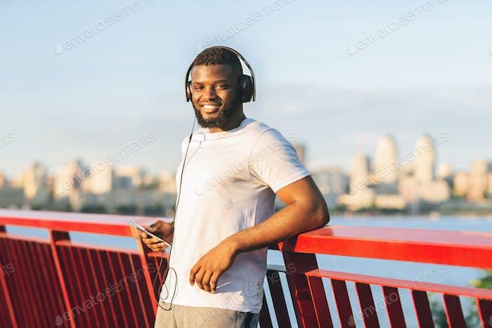 Hübscher Afro-Sportler lächelnd bei der Kamera, bleiben auf Brücke
