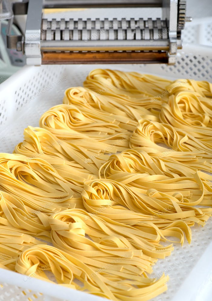 Freshly made Italian fettuccine pasta on a tray