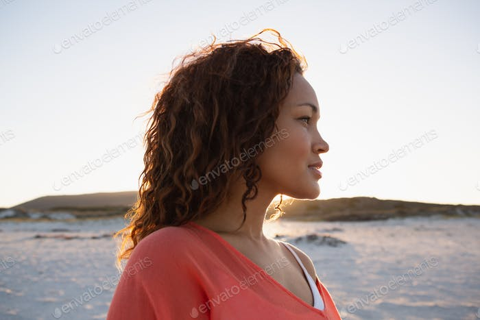 Side view of beautiful mixed race woman looking away on the beach