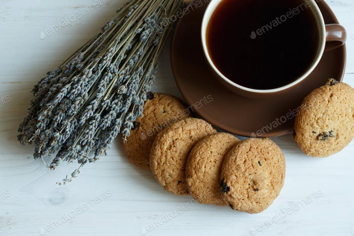 Lavender, cookies and cup of tea on white wooden background