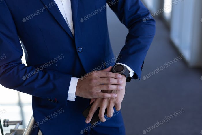 Mid section of elegant young mixed-race businessman using smartwatch standing in modern office