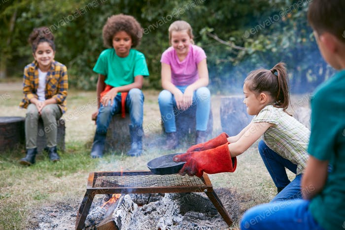 Group Of Children On Outdoor Activity Camping Trip Cooking Over Camp Fire Together