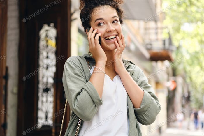 Excited woman in khaki shirt happily looking aside talking on cellphone on the street