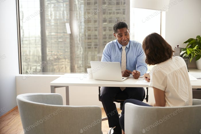 Female Client Signing Document In Meeting With Male Financial Advisor In Office
