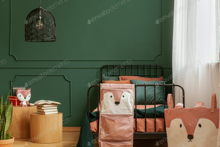 Copy space on empty dark green wall of trendy bedroom interior