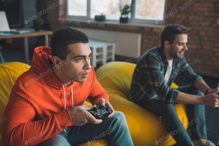 Nice young men playing play station at home