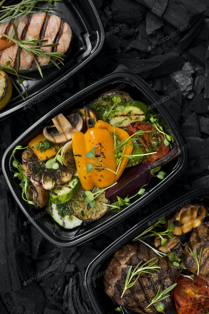 Close up of grillled vegetables, meat and fish in black boxes