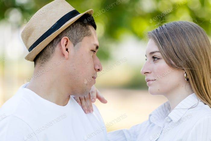 young couple looking into each other's eyes in a park. Latin man and Caucasian woman