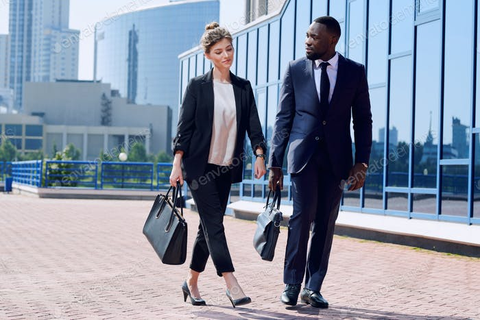 Junge interkulturelle Geschäftspartner in Formalwear, die den Bürgersteig hinunterziehen