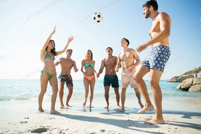 Happy friends playing soccer at beach