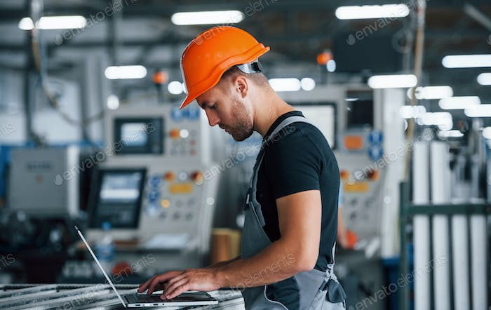 Industrial worker indoors in factory. Young technician with orange hard hat