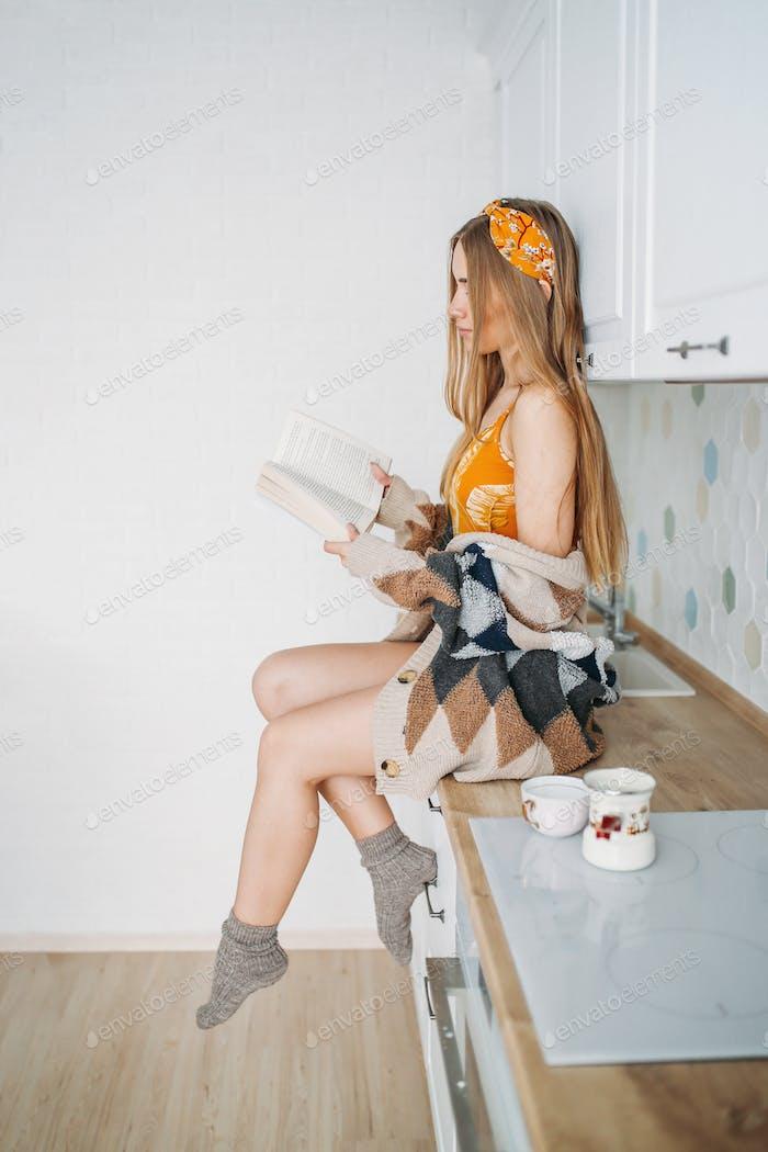 Schöne lächelnde Mädchen in gemütlichen Strickjacke Lesebuch auf Küche Arbeitsfläche zu Hause