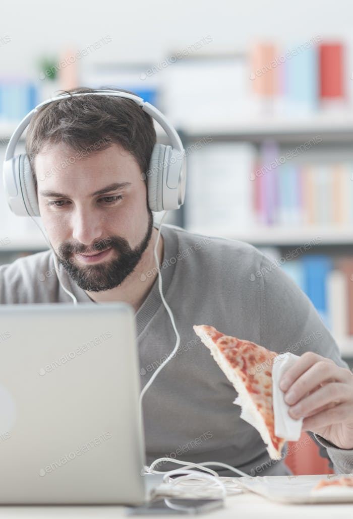 Man surfing the net and having a snack
