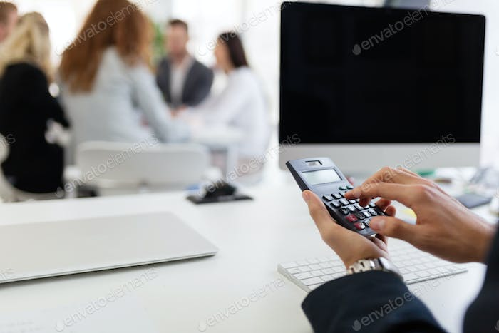 Picture of busy man using calculator in office