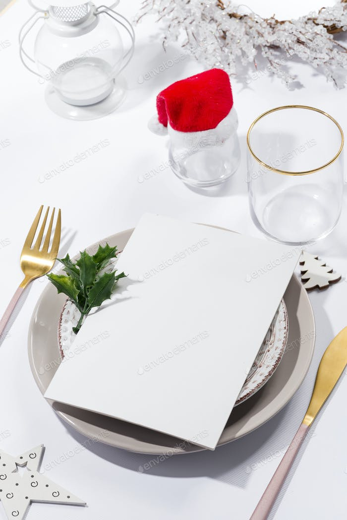 Winter festive table setting with cutlery and white brochure on table. Christmas tableware