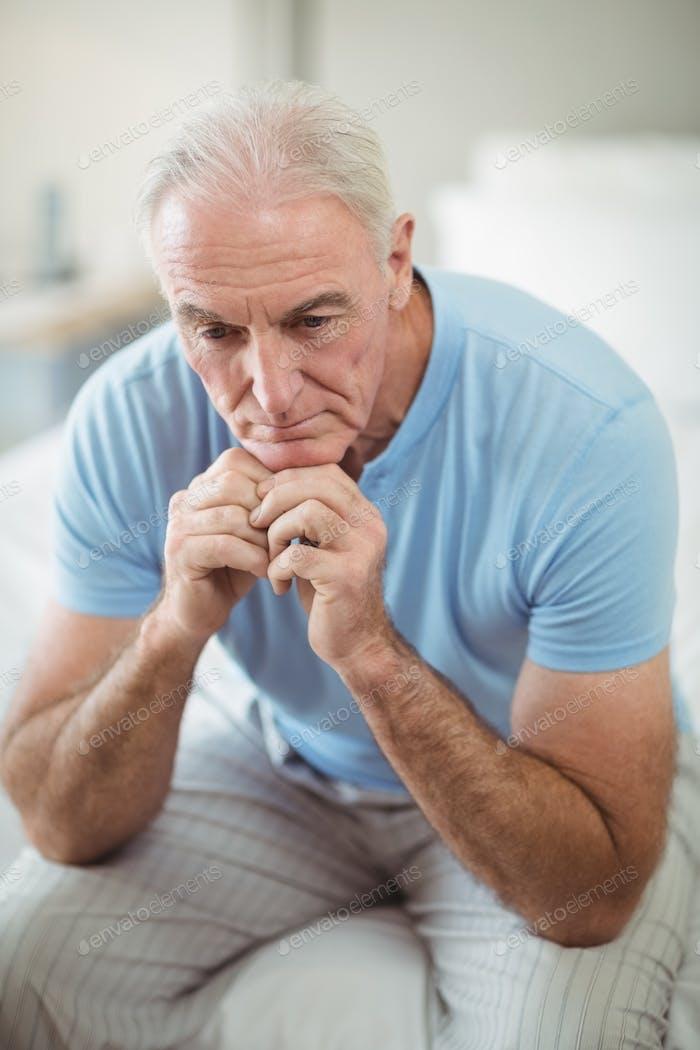 Tense senior man sitting on bed in bedroom