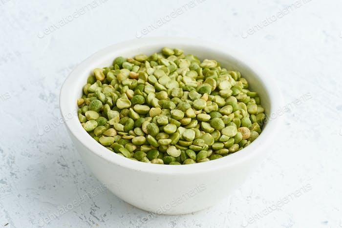 Grüne Erbsen in weißer Schüssel auf weißem Hintergrund. Getrocknete Getreide in Tasse, vegane Lebensmittel. Seitenansicht