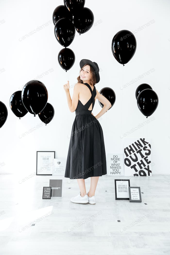 Smiling attractive young woman holding black balloons and looking back