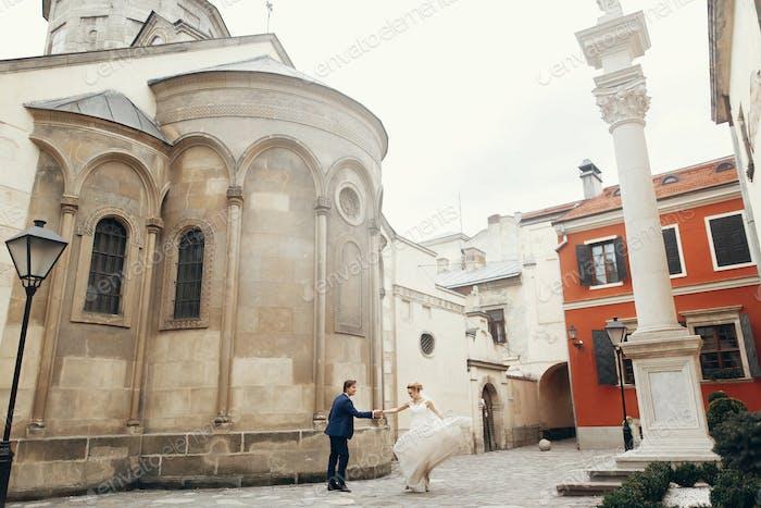 Happy emotional bride dancing outdoors with elegant groom