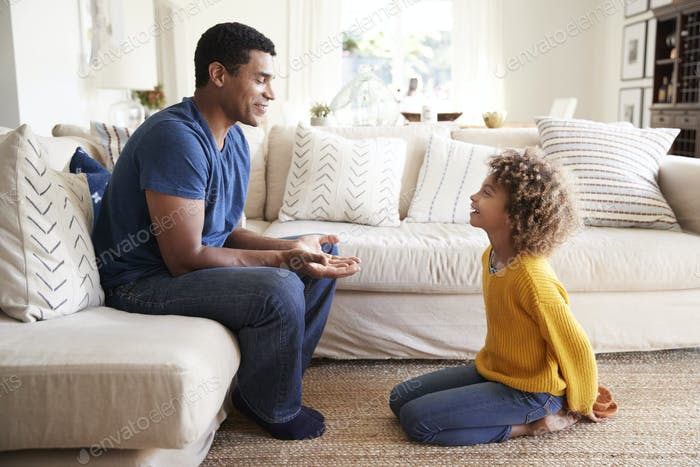 Pre-teen girl kneeling in front of her dad to give him a present she has made, close up, side view