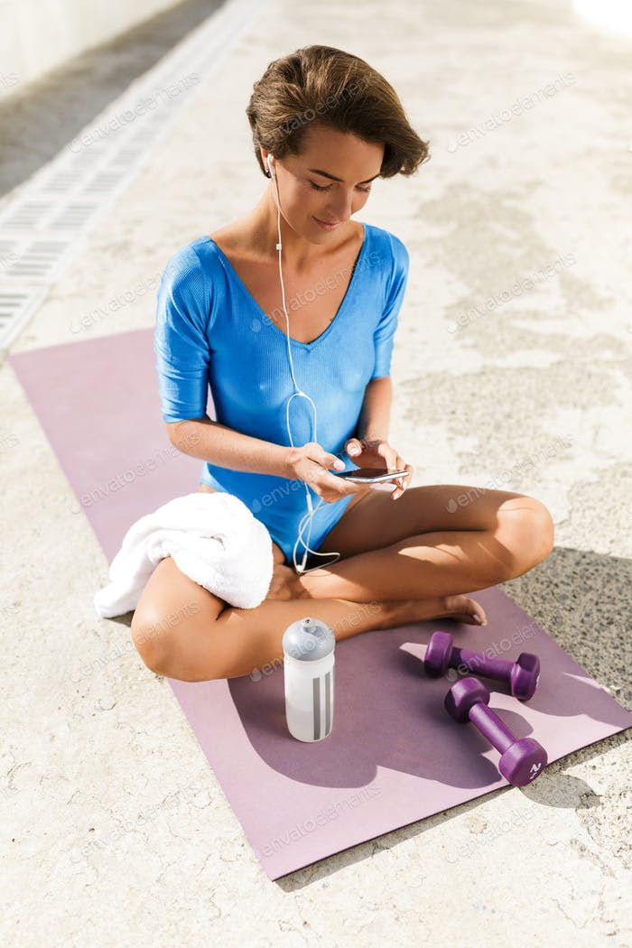 Woman with dark short hair in blue swimsuit sitting on yoga mat and listening music on her cellphone