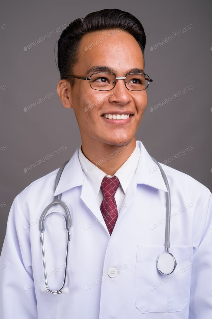 Young handsome Indian man doctor against gray background