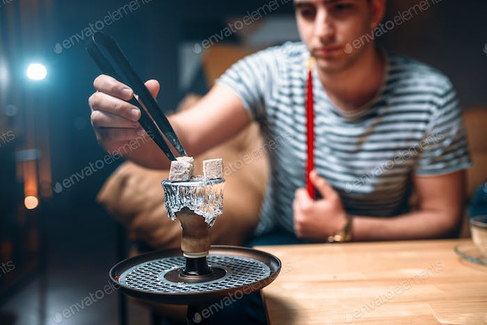 Young man with tongs kindle the coal at hookah bar
