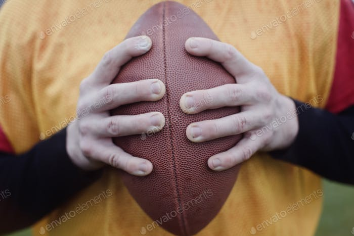 Close up of hands holding an American football.