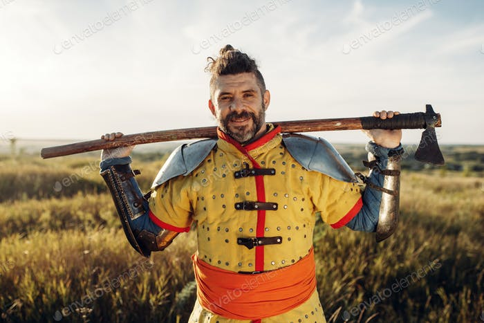 Medieval knight with axe poses in armor