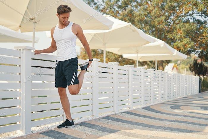 Man runner stretching legs before run