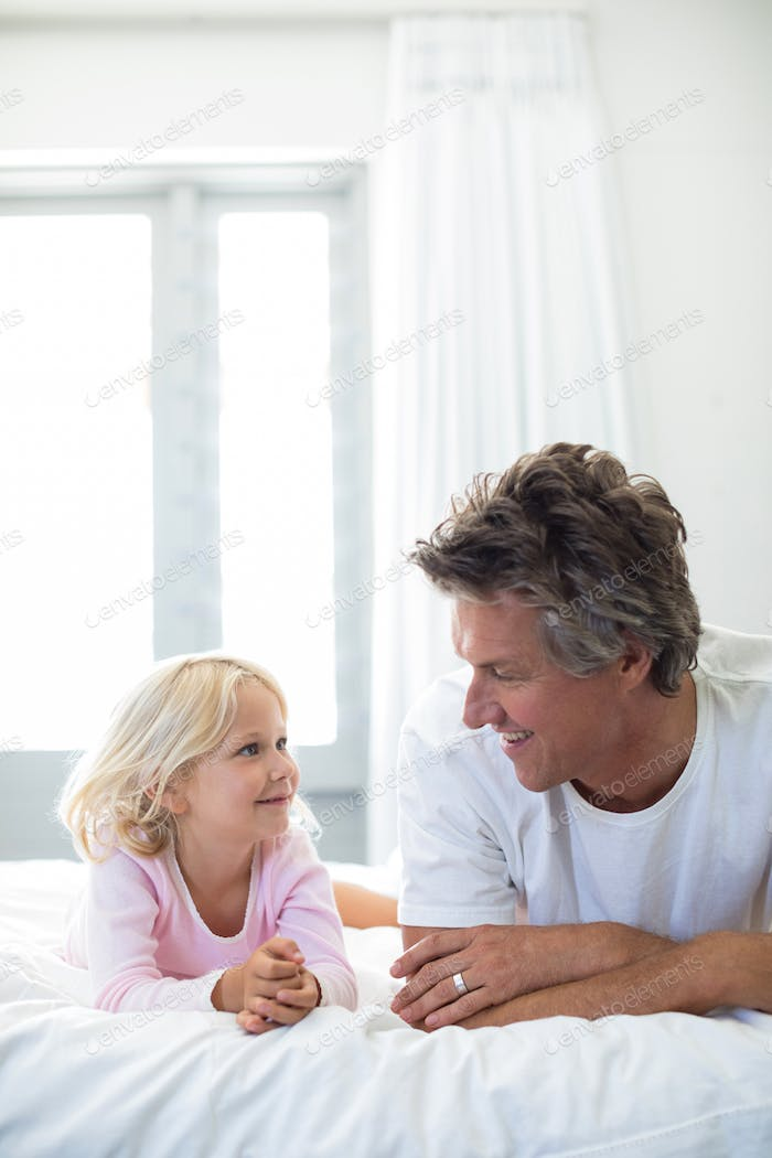 Father and daughter lying together in bedroom