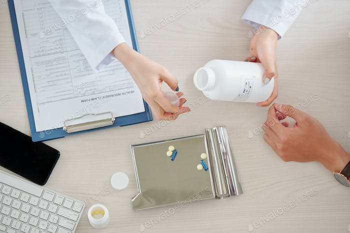 Doctor giving patient pills and tablets