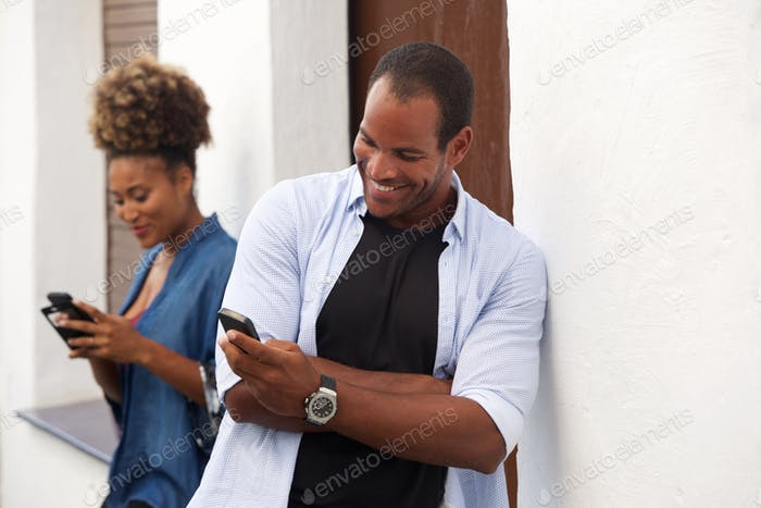 handsome couple standing and looking at mobile phones