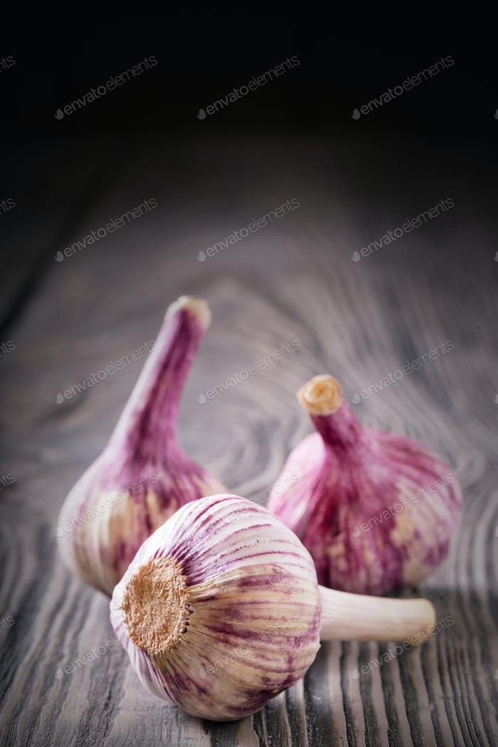 Three heads of garlic on a wooden table