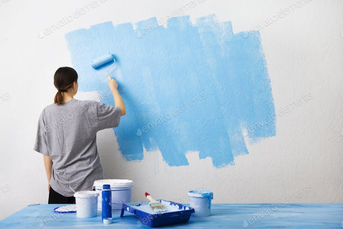 Woman painting interior wall with paint roller
