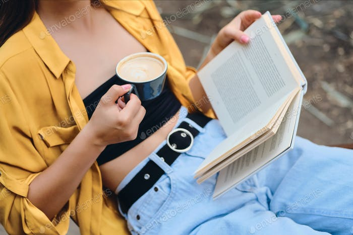 Close up woman in yellow shirt and jeans holding cup of coffee and book in hands in city park