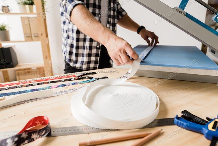Junge Designer mit Ausrüstung zum Drucken von Ornamenten auf handgefertigten Haustierhalsbändern