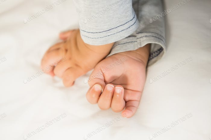 Hands of baby on bed
