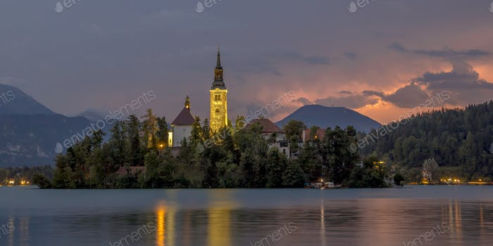 Lake bled with church under lightning in mountains