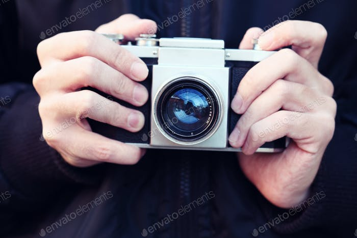 Old film camera in the hands