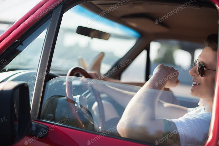 happy handsome man driving car