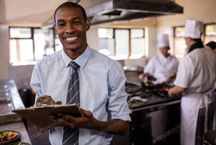 Male manager writing on a clipbaord in kitchen