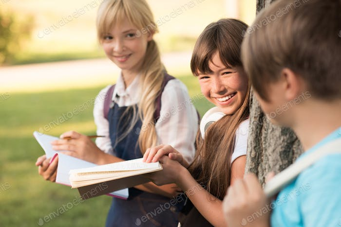 attractive smiling teenage girls studying together in park
