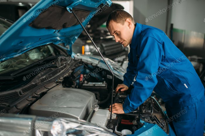 Mechanic repairs car engine, motor diagnostic